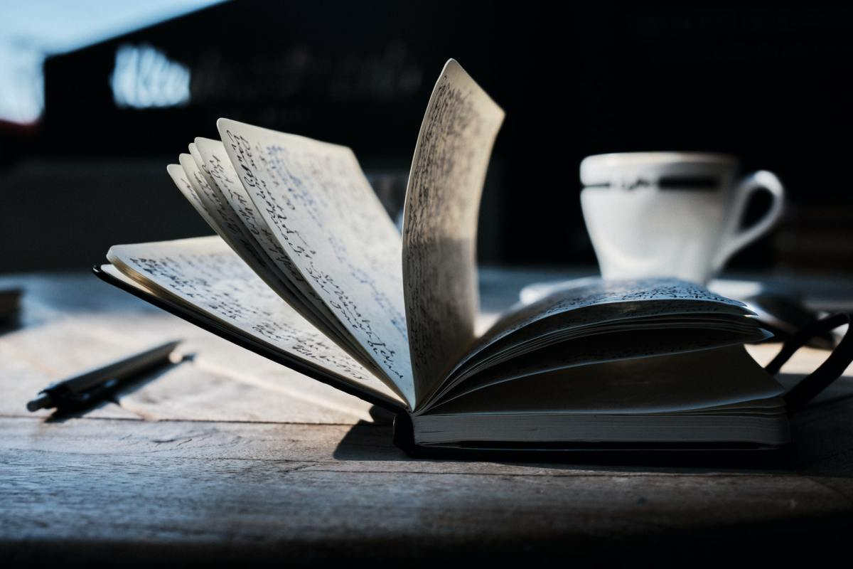 A notebook sits open on a table, pages mid-term. A tea cup rests nearby.