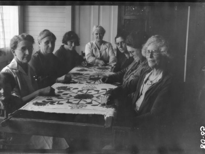 Seven women sit around a table. A quilt is laid out on the table.
