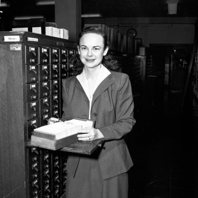Library staff member Simone Robbins stands beside a card catalog smiling at the camera. A card file rests before her. Photo taken on February 10, 1954.
