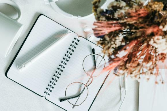 Eyeglasses rest on a opened notebook.