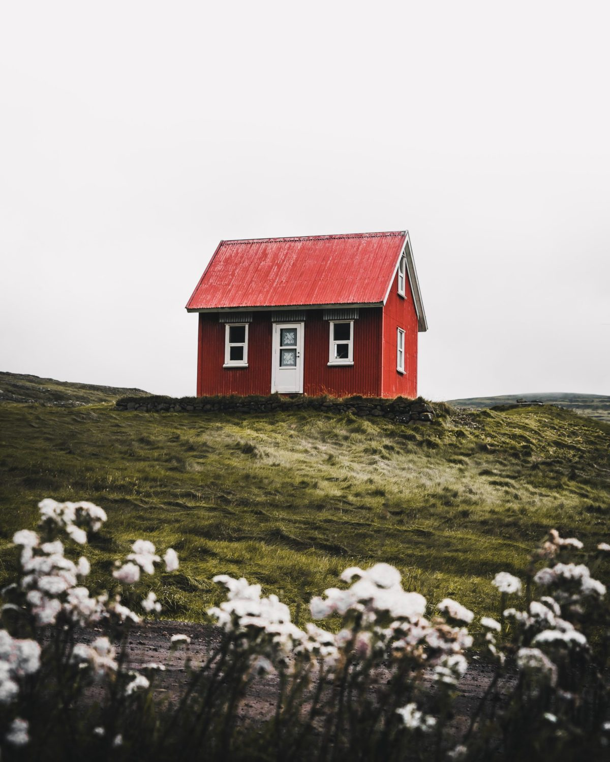A small red house sits atop a grassy hill.