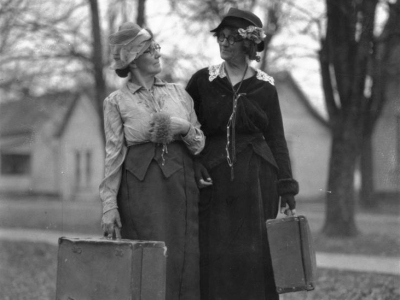 Sara and Nannie stand shoulder to shoulder with their heads turned toward one another. Both are carrying suitcases.