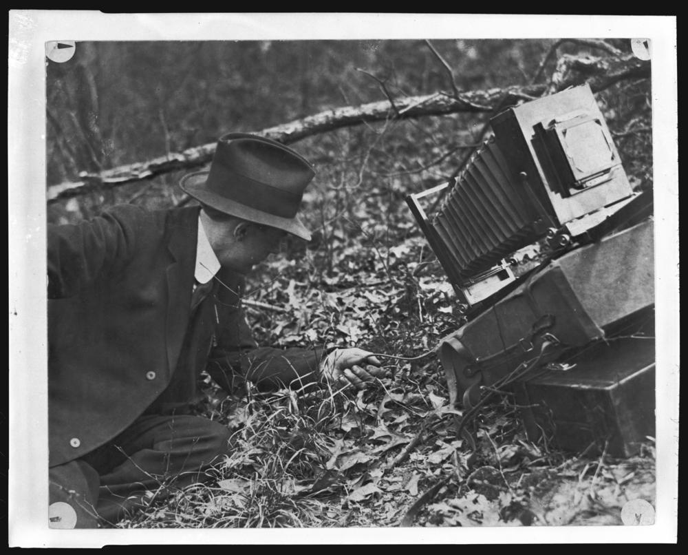 Frank M. Hohenberger lays on the ground propped on one elbow next to his camera.
